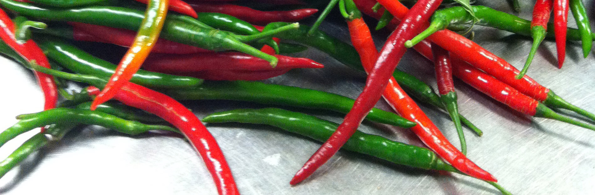 Pile of green and red hot peppers